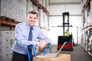 Manager with laptop on a box in a warehouse