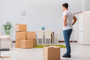 man frustrated by moving boxes alone